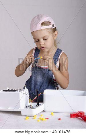 Girl tighten the screws to screw wrench, repairing toy