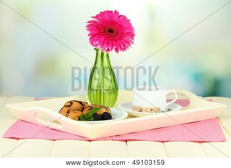 Wooden tray with breakfast, on wooden table, on light background