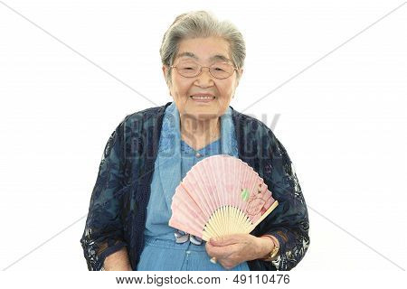 Smiling old woman with paper fan