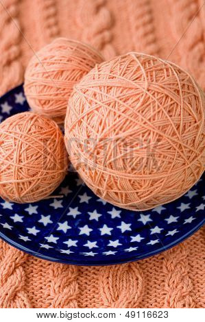 Three ball of pink yarn on talelke with asterisks