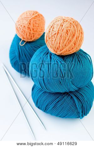 Five bright balls of yarn and two knitting needles