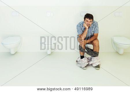 Man sitting on the toilet, public bathroom