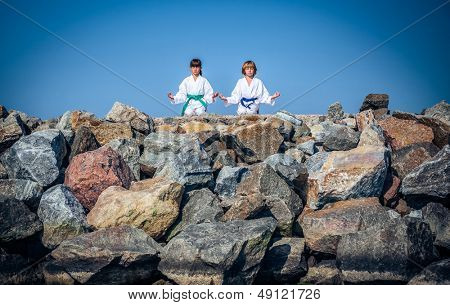 boy and girl practising yoga on beach