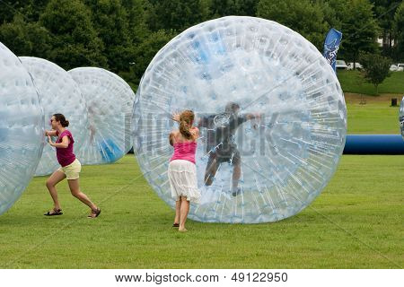 Women Push Large Zorbs Around Grass Field At Summer Festival