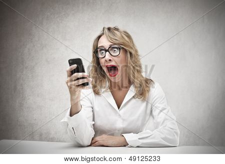 beautiful amazed woman with phone in hand