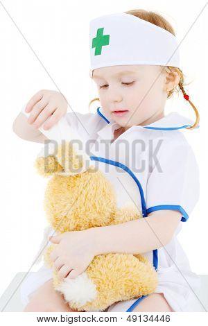 Kleines Mädchen verkleidet als Krankenschwester Kopf an Spielzeug-Hasen, isolated on white Background Bandagen.