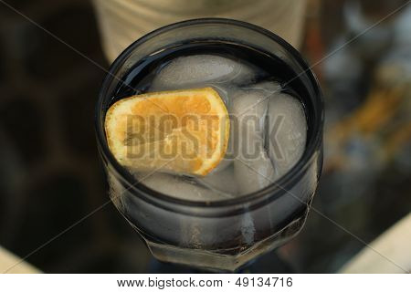 slice of lemon in blue water glass