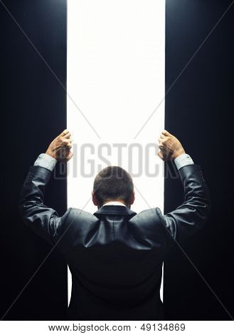 Businessman opening the gate to a bright light