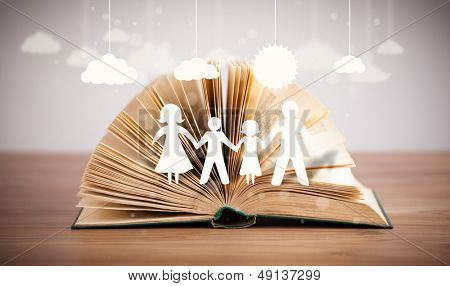 Cardboard figures of the family on opened book. The symbol of unity and happiness