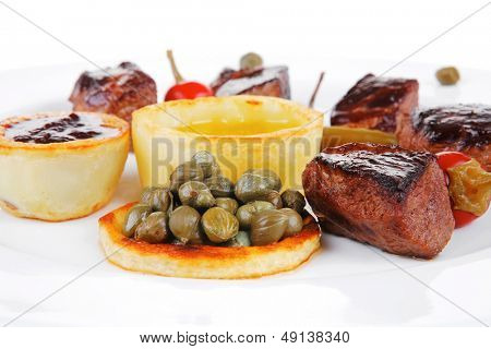 european food: roast beef meat goulash over white plate isolated on white background, with hot pepper, capers and sauces