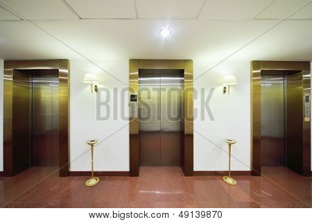 Metal doors to elevators, marble floor and high ashtrays in big stylish hotel.