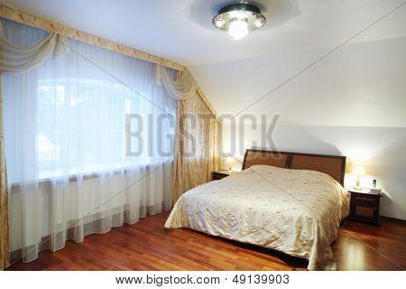 Bedroom with beautiful bed with bedside tables, big window in classic style.