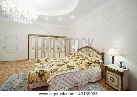 Luxurious bedroom with gilt double bed and bedside tables in classic style.