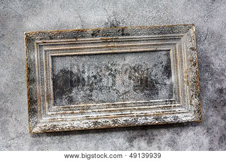 Old painting in wooden frame on wall, everything is covered with ice and snow