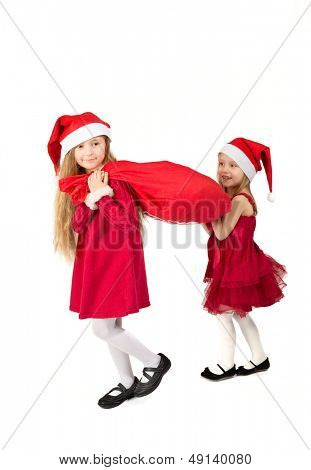 Two girls in a red dress in the bell Santa Claus dragging a bag of gifts