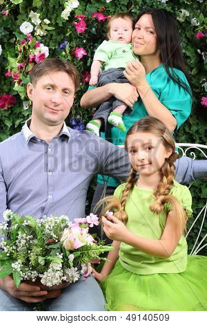 Happy family of four with bunch of flowers in garden near verdant hedge.