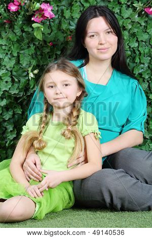 Smiling mother and little daughter sit on lawn in garden next to verdant fence.
