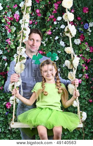 Smiling father and little girl with shamrock on head on swing in garden next to verdant fence.