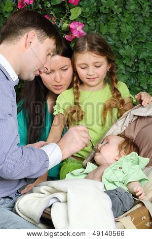 Father feeds baby, mother and daughter look at baby in garden near to verdant fence.