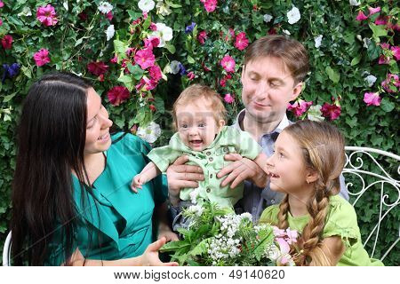 Father, mother and sister look at baby on bench in garden near verdant hedge.