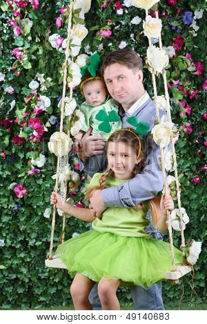 Smiling father with baby and little girl with shamrock on head on swing in garden next to verdant fence.