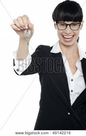 Smiling Young Business Lady Holding Up A Key