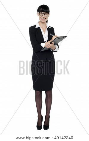 Female Secretary Jotting Down Notes On Writing Pad