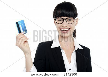 Cheerful Bespectacled Woman Holding Up Her Cash Card