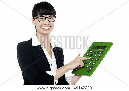 Bespectacled Woman Using Big Green Calculator