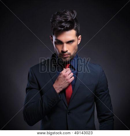 Retrato de un hombre de negocios joven mirando a la cámara mientras la fijación de su corbata. sobre un fondo negro