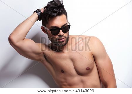 closeup of a young topless man fixing his hair while looking away from the camera. on light gray background
