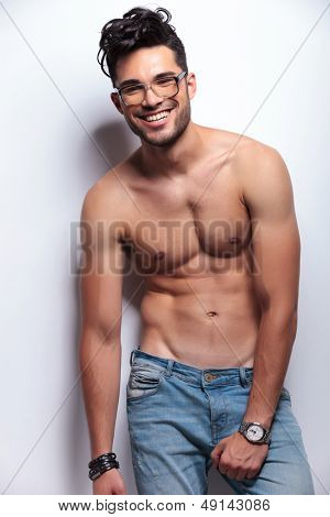 young topless man looking at the camera while holding his hand on his crotch and smiling. on light gray background