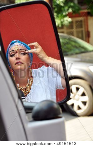 Senior Woman With Indian Jewlery Looking At Car Mirrow In The Street