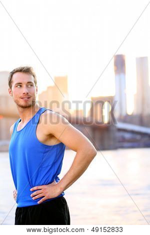Sport athlete looking resting in New York City after running and training fitness workout outdoor in New York with Brooklyn Bridge and Manhattan skyline in background. Fit male fitness runner outside.