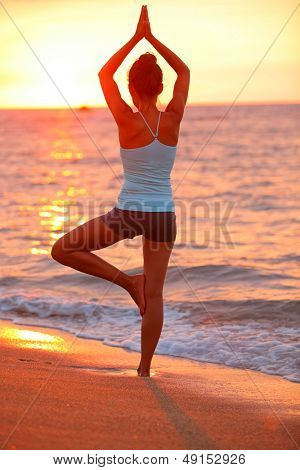 Yoga meditation woman meditating at beach sunset relaxing in yoga posture, tree pose, vrksasana. Relaxed serene Asian woman enjoying evening sun light and sunshine. From Big Island, Hawaii, USA.