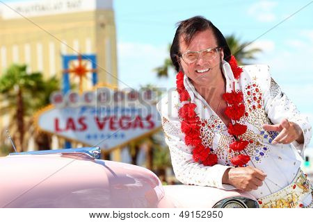 Las Vegas Elvis impersonator on the strip pointing looking at camera in front of Welcome to Fabulous Las Vegas sign and car.