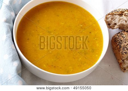 Bowl of vegetable soup with bread on side, placed on white table cloth