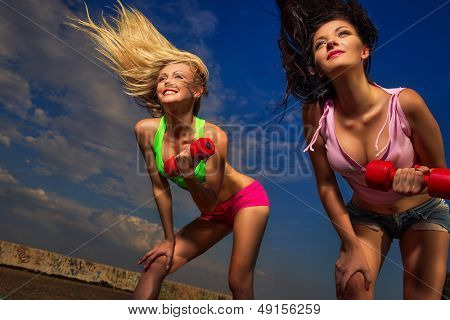 Two young fit women lifting dumbbells against sky