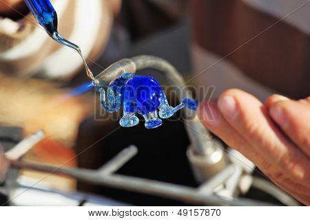 Heikle Arbeit des Gebläses Glas. Das Künstler-Glas-Gebläse erzeugt eine anmutige kleine Figur von ein ele