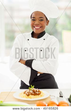 pretty female african chef with arms crossed standing in hotel kitchen