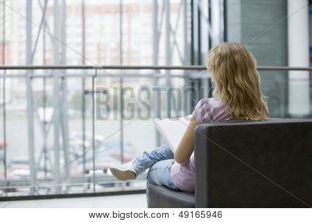 Rear view of young woman with magazine sitting on sofa in shopping mall