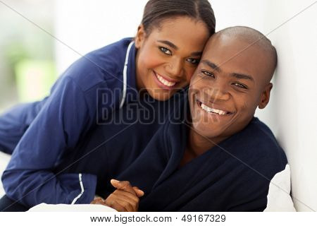 portrait of happy african couple in nightwear on bed