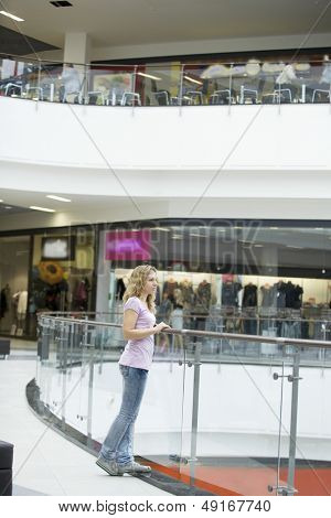 Thoughtful young woman standing by railing in shopping mall