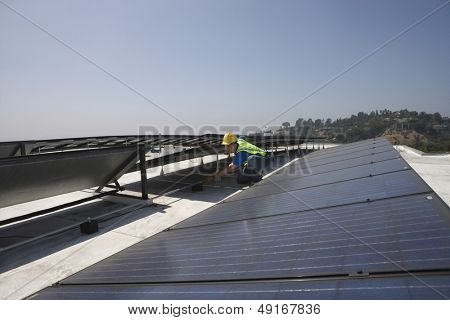 Young maintenance worker checking solar panels on rooftop