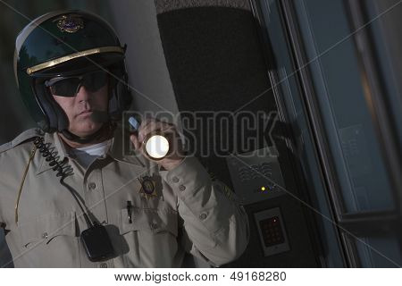 Middle aged traffic cop investigating with flashlight at night