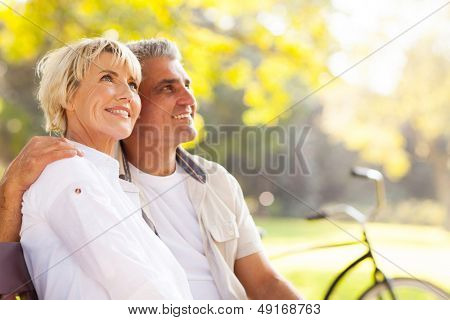 elegant mature couple sitting on a bench outdoors