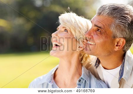 happy middle aged couple bird watching outdoors