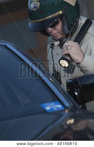 Middle aged traffic cop with flashlight investigating car