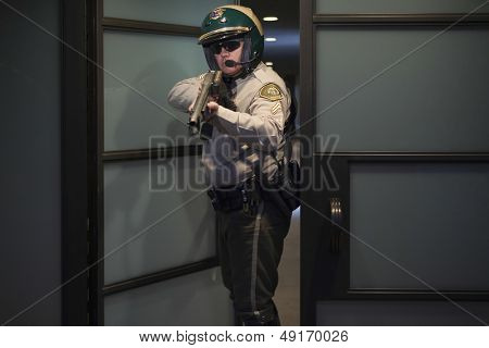 Confident middle aged traffic cop aiming rifle while standing at door
