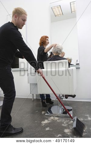 Young man sweeping while hairdresser giving haircut to senior woman in salon